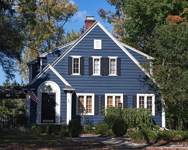 small house with blue wood siding and white windows