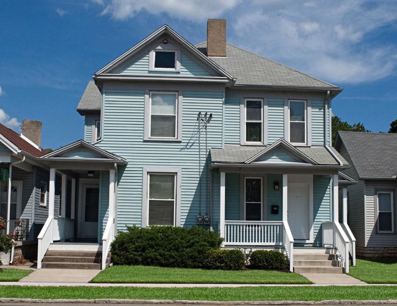 Old blue house that has been renovated & turned into a duplex with twin front entrances and steps