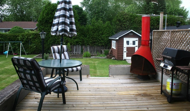 Patio In Rear Of Home From the balcony with red fireplace we can see a garden cabana and swings