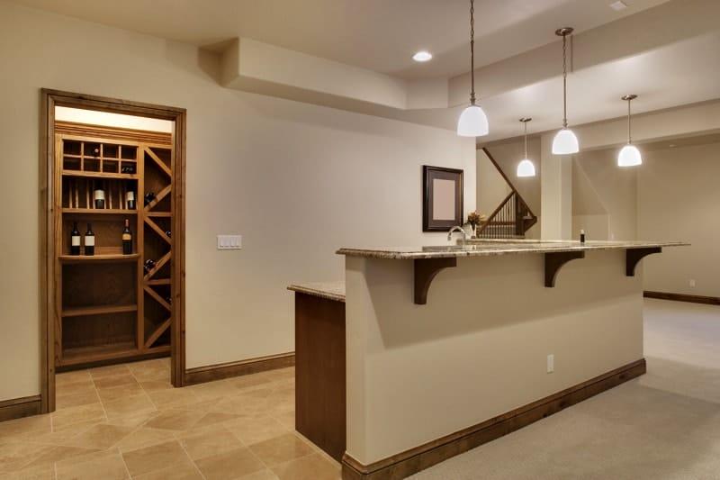 basement bar area with tiled floor wine storage area and overhead bar