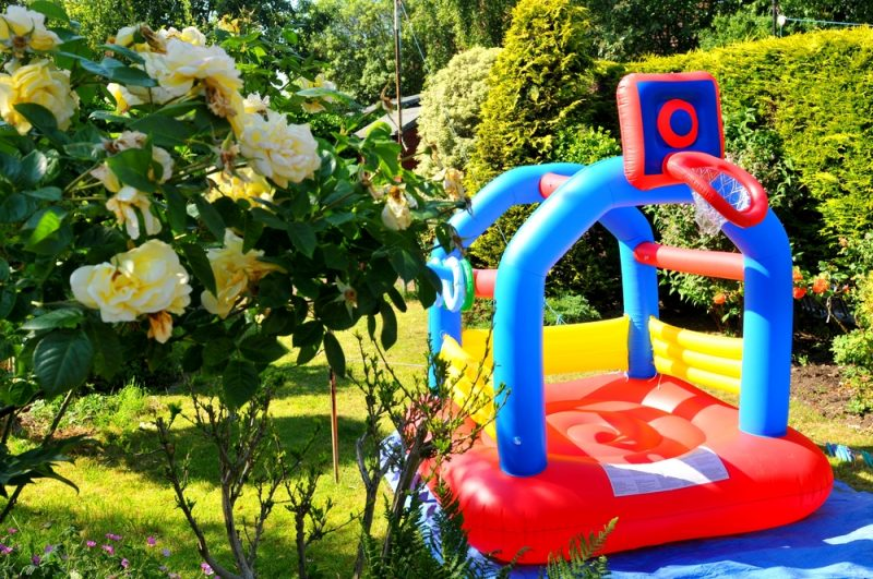Colorful bouncing castle in the garden e1500699158270 - Childrens' Outdoor Play Equipment