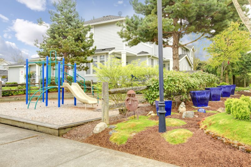 Siding house with small play yard for kids and beautiful flower bed and decorated blue flower pots e1500699512692 - Childrens' Outdoor Play Equipment