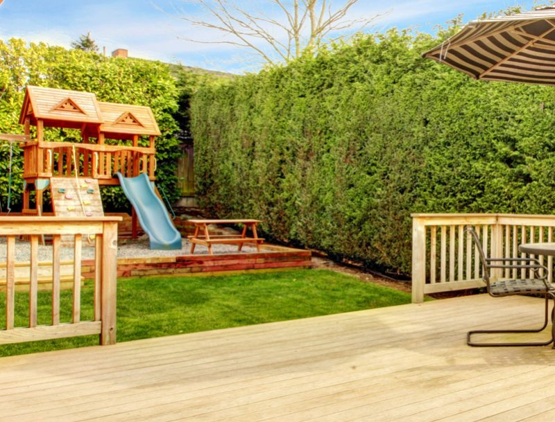 Spacious wooden deck with umbrella and patio table set. View of play yard with chute e1500699722976 - Childrens' Outdoor Play Equipment